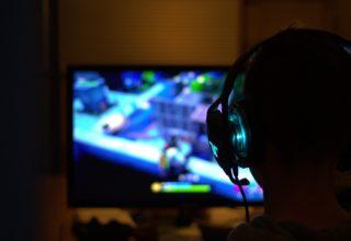 Mężczyzna gra na komputerze. Komputer z wynajmu komputerów gamingowych.
